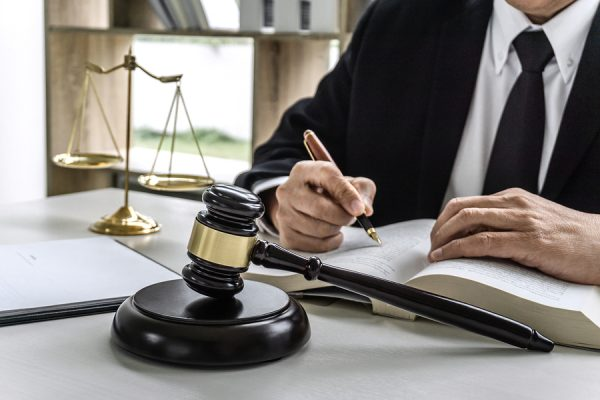 A wrongful death attorney Sugar Land, TX reviewing legal cases at his desk with a gavel and scales of justice on it.